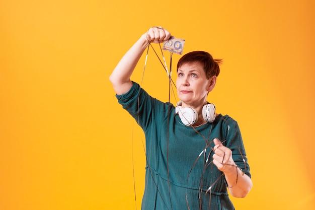 Mujer senior divertida mirando una cinta de cassette