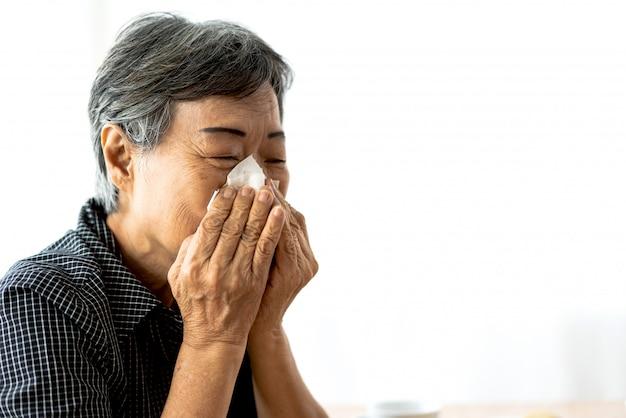 Mujer senior enferma sonarse la nariz con pañuelos de papel y estornudar mientras tiene resfriado.
