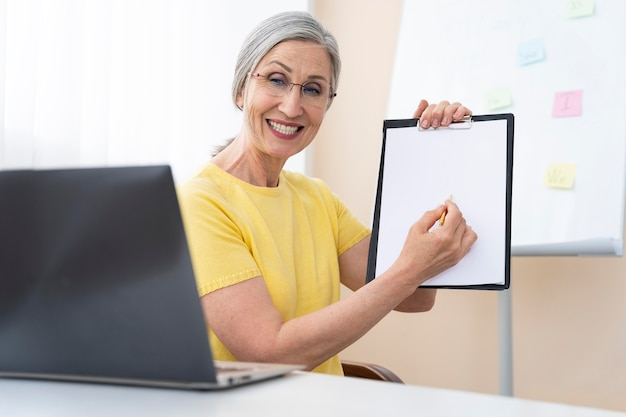 Mujer senior enseñando lecciones de inglés
