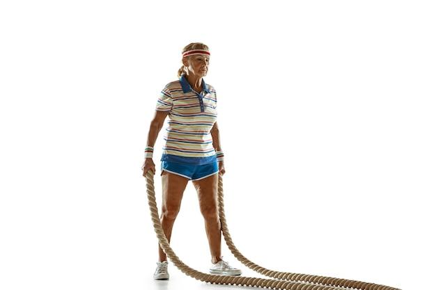 Mujer senior entrenando con cuerdas en ropa deportiva sobre pared blanca