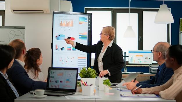Mujer senior experimentada directora de tecnología de tecnología de la empresa de nueva creación que comparte informes financieros sobre la estrategia del proyecto y brinda información a un grupo diverso de inversores. empresarios multiétnicos que trabajan en finanzas de inicio profesional
