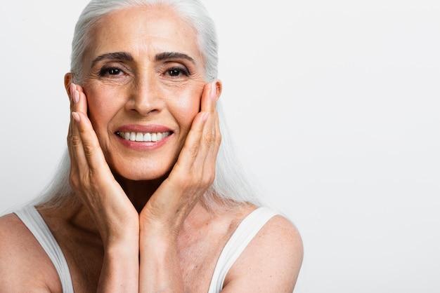 Mujer senior feliz aplicando crema para el cuidado de la piel