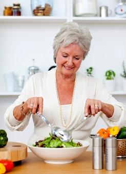 Mujer senior feliz cocinando una ensalada