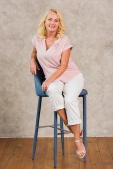 Mujer senior feliz mirando a la cámara mientras está sentado en la silla