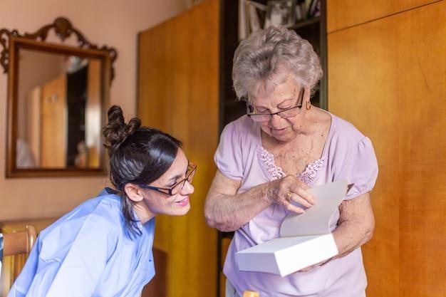 Mujer senior feliz con su cuidador en casa leyendo un libro