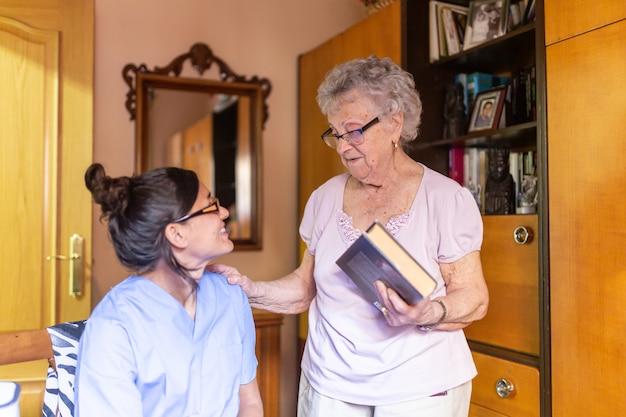 Mujer senior feliz con su cuidador en casa sosteniendo un libro