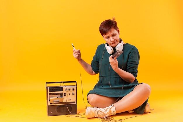 Mujer senior hipster mirando un cassette