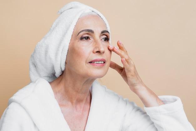 Mujer senior limpia en bata de baño