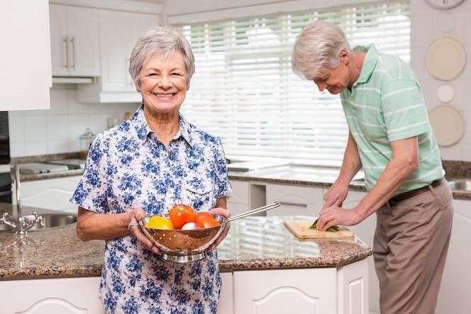 Mujer senior mostrando colador de verduras