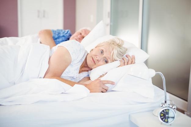 Mujer senior pensativa acostada además del hombre en la cama