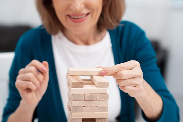Mujer senior de primer plano jugando jenga