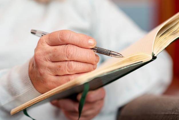 Mujer senior de primer plano tomando notas