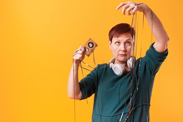 Mujer senior sacando cinta de un cassette