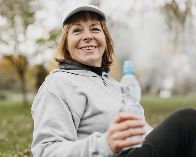 Mujer senior sonriente agua potable al aire libre después de hacer ejercicio