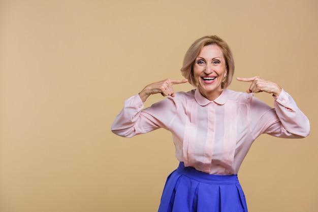 Mujer senior sonriente apuntando a sí misma
