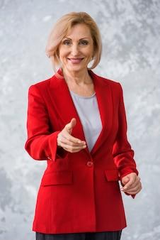 Mujer senior sonriente dando un apretón de manos