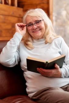 Mujer senior sonriente leyendo en casa