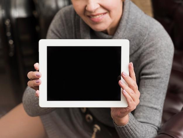 Mujer senior sonriente sosteniendo una tableta vacía
