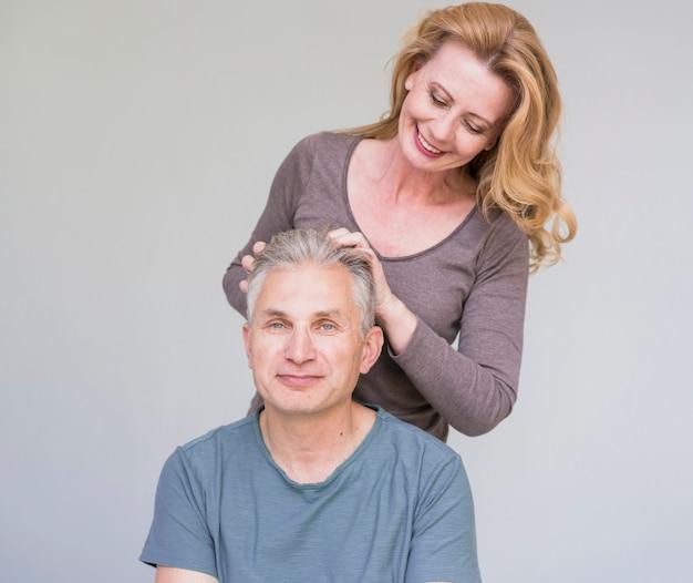 Mujer senior sonriente tocando cabello de maridos