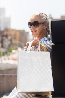 Mujer senior de tiro medio sosteniendo el bolso