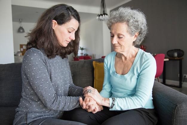Mujer senior tranquila y su hija sentada y tomados de la mano