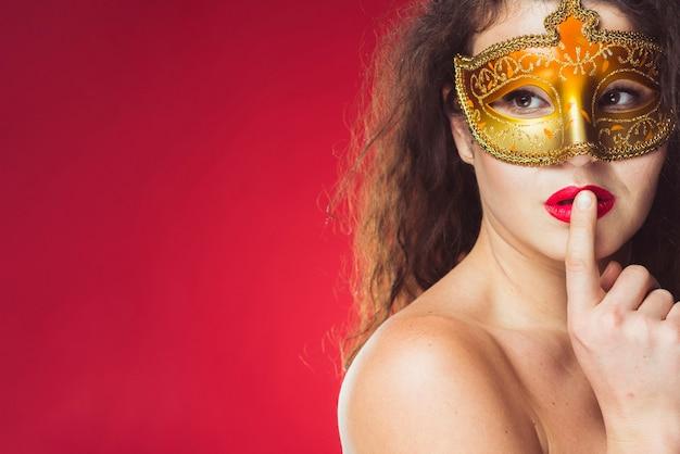 Mujer sensual atractiva en máscara de oro