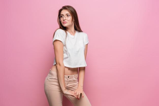 Mujer sensual bastante joven de la moda atractiva que presenta en la pared rosada vestida en vaqueros del estilo inconformista