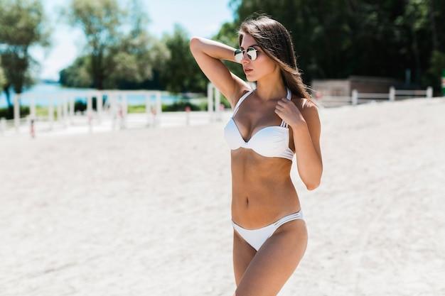 Mujer sensual en bikini mirando a otro lado