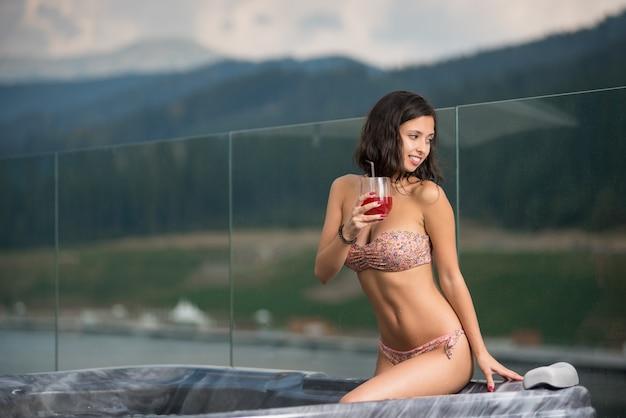 Mujer sensual con cuerpo perfecto en bikini sentada en el jacuzzi con un cóctel y mirando a otro lado contra el fondo borroso de la naturaleza