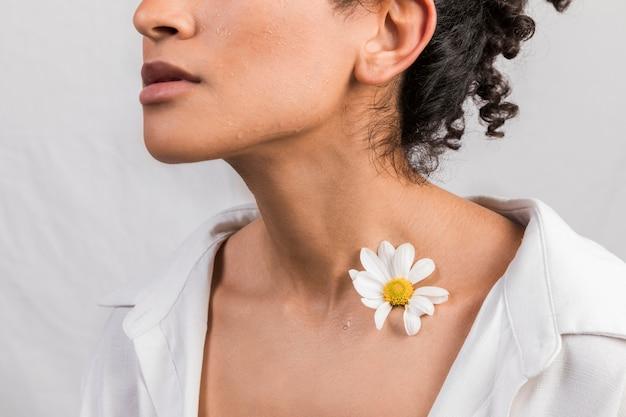 Mujer sensual con flor en el cuello.