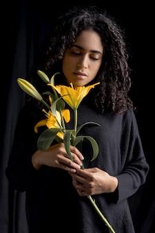Mujer sensual con flores amarillas en la oscuridad
