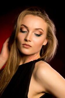 Mujer sensual con maquillaje profesional y exuberante cabello rubio en el estudio