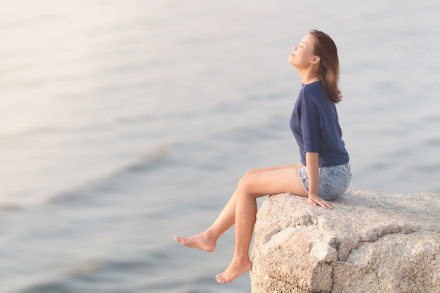 Mujer sentada en el acantilado de roca y respirando aire fresco.