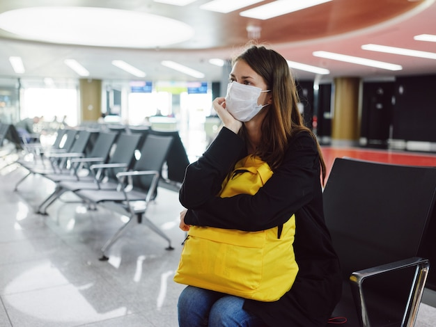 Mujer sentada en el aeropuerto con equipaje en una máscara médica esperando un vuelo