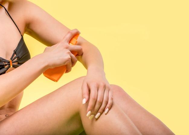 Mujer sentada y aplicando protector solar sobre la piel.
