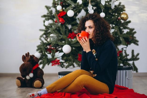 Mujer sentada por el árbol de navidad y bebiendo té