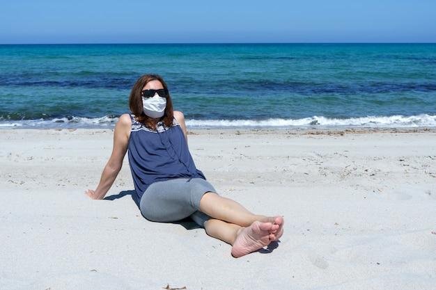 Una mujer sentada en la arena en la playa mira al sol con la máscara para la pandemia de coronavirus covid-19