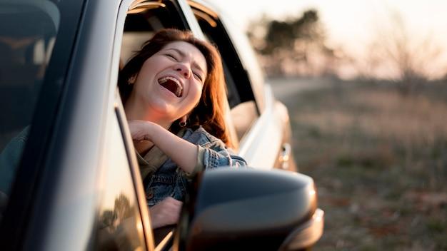 Mujer sentada en un auto y riendo