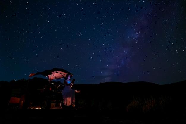 Una mujer sentada en el automóvil de un granjero, mirando las estrellas en el cielo nocturno, con la vía láctea de fondo.