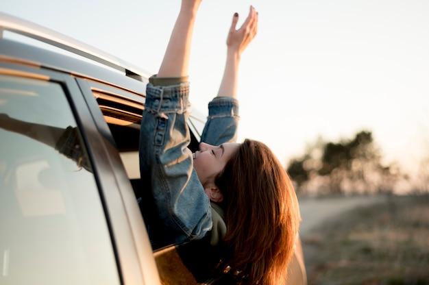 Mujer sentada en un automóvil con las manos y la cabeza al aire libre