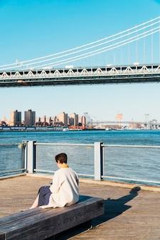 Mujer sentada en un banco cerca de la costa