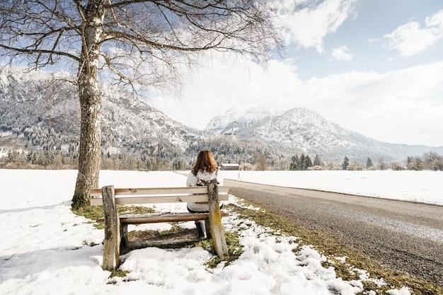 Mujer sentada en el banco de madera y mirando las montañas cubiertas de nieve bajo el cielo nublado