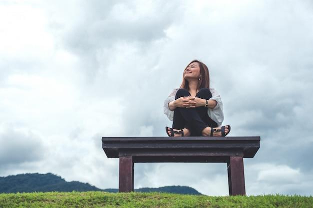 Una mujer sentada en un banco de madera en la naturaleza