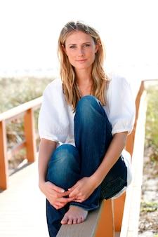 Mujer sentada en la barandilla del camino de la playa sonriendo