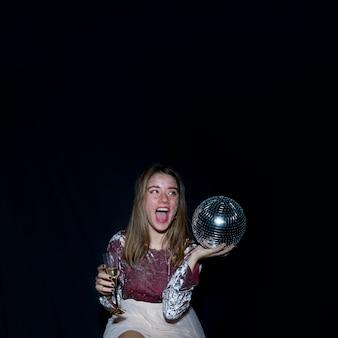 Mujer sentada con bola de discoteca en la mano