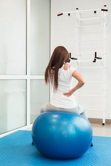 Mujer sentada en bola de terapia