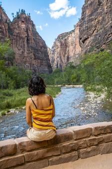 Mujer sentada en el borde de piedra cerca del río en el angels landing trail en el parque nacional zion