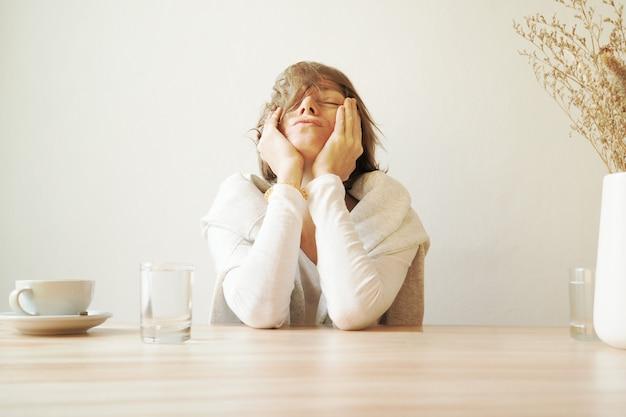 Mujer sentada en un café con dientes ach
