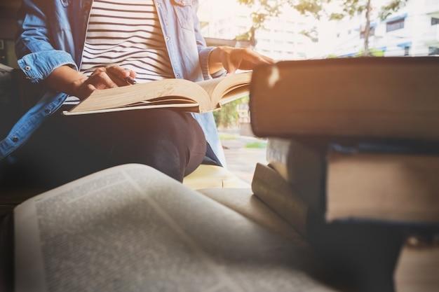 Mujer sentada en un café, leyendo el libro