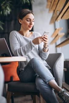 Mujer sentada en un café tomando café y trabajando en una computadora